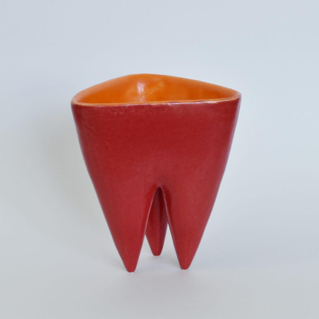 Tripod Vessel glazed red with orange glaze inside.
